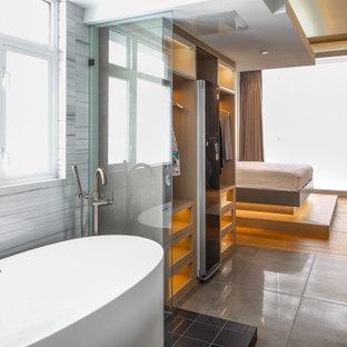 Idee per un'ampia cabina armadio unisex design con ante di vetro, ante in legno chiaro, pavimento in cemento e pavimento nero