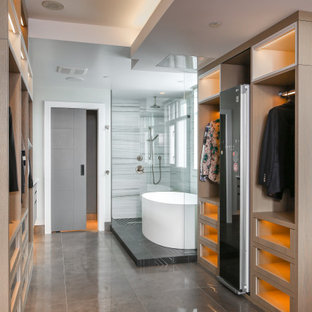 Ispirazione per un'ampia cabina armadio unisex minimal con ante di vetro, ante in legno chiaro, pavimento in cemento e pavimento nero