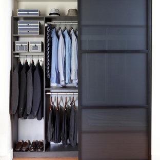 Ejemplo de armario unisex, contemporáneo, de tamaño medio, con suelo de madera clara y puertas de armario grises