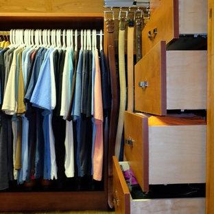 Ejemplo de armario vestidor de hombre, contemporáneo, pequeño, con armarios con paneles lisos, puertas de armario de madera oscura y suelo de madera clara