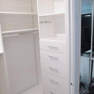 Immagine di una piccola cabina armadio unisex minimalista con ante lisce e ante bianche