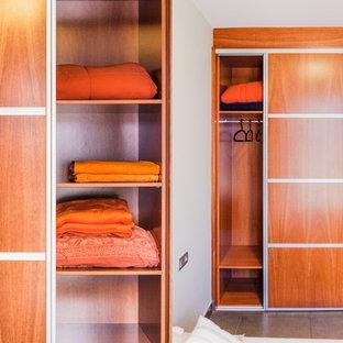 Ejemplo de armario y vestidor actual con puertas de armario de madera oscura y suelo de baldosas de porcelana