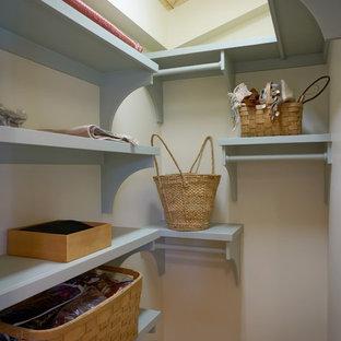 Foto de armario y vestidor costero, pequeño, con armarios estilo shaker, puertas de armario verdes y suelo de madera clara