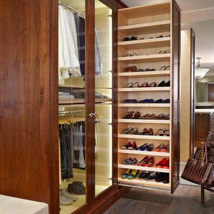 Aménagement d'un dressing et rangement classique neutre avec des portes de placard en bois sombre et un sol en bois foncé.