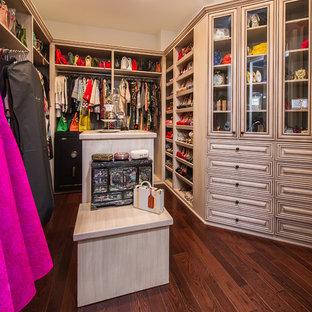 Diseño de armario vestidor de mujer, mediterráneo, grande, con armarios con paneles con relieve, puertas de armario de madera clara y suelo de madera oscura