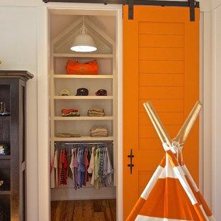 Imagen de armario y vestidor costero con puertas de armario blancas y suelo de madera en tonos medios