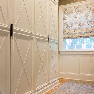 Modelo de vestidor unisex, tradicional renovado, pequeño, con armarios con paneles empotrados, puertas de armario blancas y suelo de madera clara