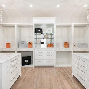Imagen de armario vestidor unisex, contemporáneo, extra grande, con armarios con paneles lisos, puertas de armario blancas, suelo de madera clara y suelo beige