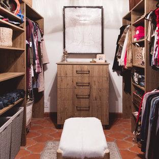 サンディエゴの広い男女兼用サンタフェスタイルのおしゃれなウォークインクローゼット (フラットパネル扉のキャビネット、中間色木目調キャビネット、テラコッタタイルの床、オレンジの床) の写真