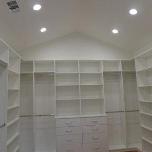 Diseño de armario vestidor unisex y abovedado, de estilo de casa de campo, extra grande, con armarios con paneles lisos, puertas de armario blancas, suelo de madera clara y suelo marrón