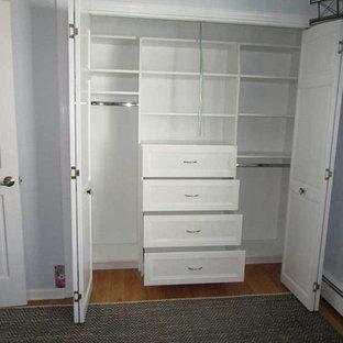 Imagen de armario de hombre, actual, pequeño, con puertas de armario blancas, suelo de madera en tonos medios y suelo marrón
