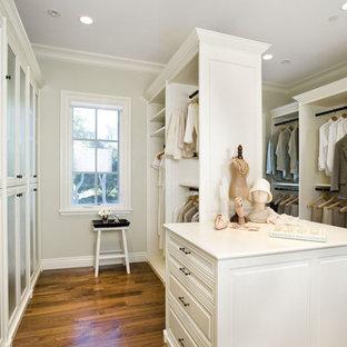 Foto di un ampio spazio per vestirsi unisex con ante con riquadro incassato, ante bianche e pavimento in legno massello medio
