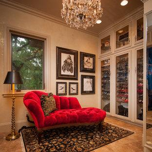 Foto di un ampio spazio per vestirsi per donna chic con ante di vetro, ante beige e pavimento in travertino