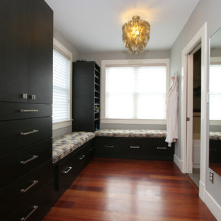 Photo of a mid-sized transitional gender-neutral walk-in wardrobe in Boston with flat-panel cabinets, black cabinets, medium hardwood floors and brown floor.