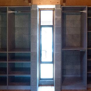Ejemplo de vestidor unisex, bohemio, con armarios con paneles lisos, puertas de armario grises y suelo de madera en tonos medios