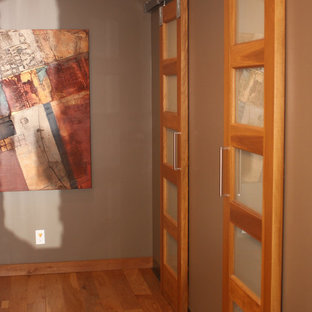 Design ideas for a large eclectic gender-neutral walk-in wardrobe in Cleveland with light hardwood floors.