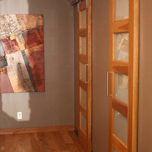 Idee per una grande cabina armadio unisex bohémian con parquet chiaro