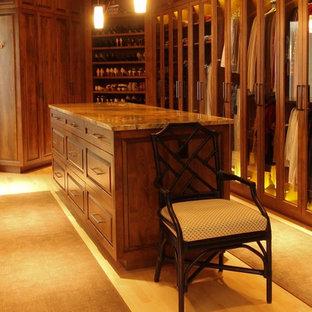Cette photo montre un très grand dressing éclectique neutre avec un placard avec porte à panneau surélevé, des portes de placard en bois brun et un sol en bois clair.