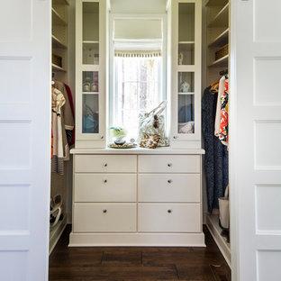 Lantlig inredning av ett walk-in-closet för kvinnor, med släta luckor, vita skåp och mörkt trägolv