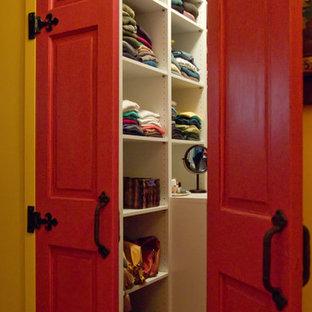 Réalisation d'un dressing sud-ouest américain de taille moyenne et neutre avec un placard sans porte, des portes de placard blanches, un sol en bois brun et un sol marron.