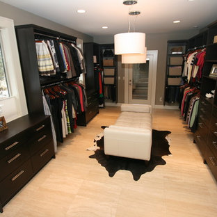 Photo of a large contemporary gender neutral walk-in wardrobe in Seattle with flat-panel cabinets, dark wood cabinets and travertine flooring.