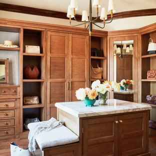 Inspiration for a large mediterranean women's dressing room in Los Angeles with recessed-panel cabinets, medium wood cabinets, medium hardwood floors and brown floor.
