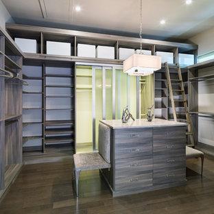 Foto di una cabina armadio unisex moderna di medie dimensioni con ante lisce, ante in legno bruno e pavimento in legno massello medio
