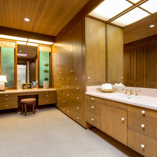 Photo of an expansive midcentury gender-neutral dressing room in Seattle with flat-panel cabinets, medium wood cabinets, carpet and beige floor.