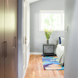 Modelo de vestidor unisex y abovedado, contemporáneo, pequeño, con armarios con paneles lisos, puertas de armario de madera en tonos medios, suelo de madera clara y suelo marrón