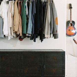 Immagine di un piccolo spazio per vestirsi per uomo industriale con pavimento in cemento e pavimento bianco