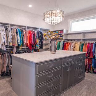 Cette image montre un grand dressing minimaliste pour une femme avec un placard à porte affleurante, des portes de placard grises, moquette et un sol gris.