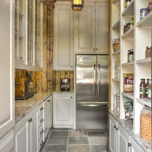 Diseño de armario vestidor rural con armarios con paneles con relieve, puertas de armario blancas y suelo de pizarra