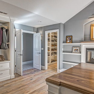 Photo of an expansive transitional gender-neutral dressing room in Denver with beaded inset cabinets, white cabinets and light hardwood floors.