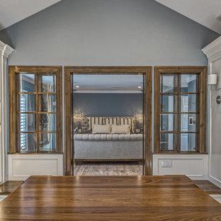 Modelo de vestidor unisex, tradicional renovado, extra grande, con armarios con rebordes decorativos, puertas de armario blancas y suelo de madera clara