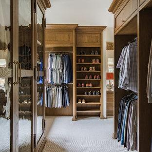 Diseño de vestidor de hombre, clásico, grande, con armarios con rebordes decorativos, moqueta y puertas de armario de madera oscura