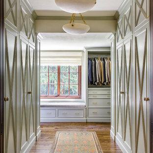 Inspiration pour un grand dressing traditionnel neutre avec un placard à porte affleurante, des portes de placards vertess et un sol en bois brun.