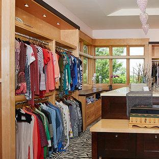 Idee per un ampio spazio per vestirsi per donna american style con ante con riquadro incassato, ante in legno chiaro e moquette