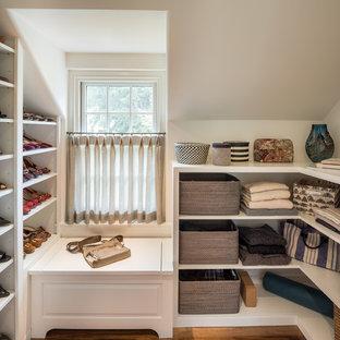 Bild på ett vintage walk-in-closet, med öppna hyllor, vita skåp, mellanmörkt trägolv och brunt golv
