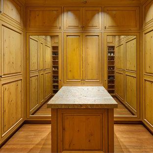 Foto di un ampio spazio per vestirsi per uomo classico con ante a filo, ante in legno chiaro e pavimento in legno massello medio