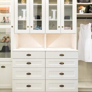 Modelo de armario vestidor de mujer, de tamaño medio, con armarios estilo shaker, puertas de armario de madera clara, suelo de madera clara y suelo gris