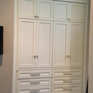 Foto de armario unisex, clásico, pequeño, con armarios con paneles empotrados, puertas de armario blancas y suelo de madera oscura