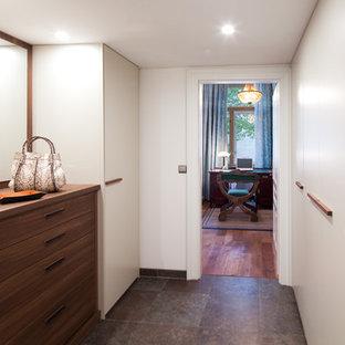 Modelo de armario vestidor de mujer, tradicional renovado, grande, con armarios con paneles lisos, puertas de armario blancas y suelo de pizarra