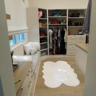 Modelo de vestidor abovedado, actual, grande, con armarios abiertos, puertas de armario blancas, suelo de madera en tonos medios y suelo blanco
