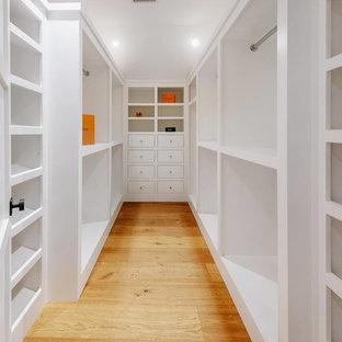 Idee per una cabina armadio unisex country di medie dimensioni con nessun'anta, ante bianche, pavimento in legno massello medio e pavimento marrone