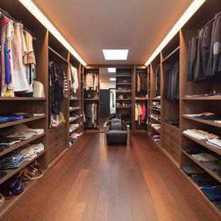 Imagen de vestidor unisex, actual, grande, con armarios con paneles lisos, puertas de armario de madera oscura, suelo de madera en tonos medios y suelo marrón