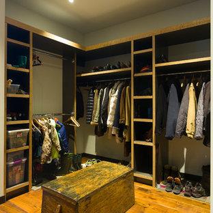 Idee per un ampio spazio per vestirsi unisex minimal con nessun'anta, ante con finitura invecchiata, pavimento in legno massello medio e pavimento marrone