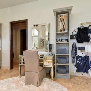 Imagen de vestidor de mujer, clásico renovado, extra grande, con armarios abiertos, puertas de armario grises, suelo de piedra caliza y suelo beige