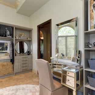 サクラメントの巨大な女性用トランジショナルスタイルのおしゃれなフィッティングルーム (オープンシェルフ、グレーのキャビネット、ライムストーンの床、ベージュの床) の写真