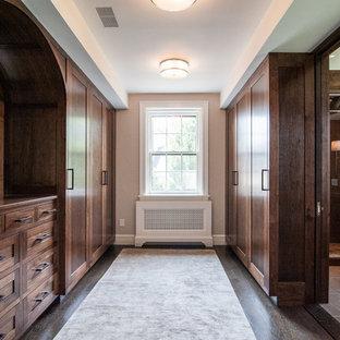 Idee per una grande cabina armadio unisex stile americano con ante in stile shaker, ante in legno bruno e parquet scuro