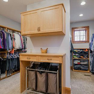 Réalisation d'un très grand dressing chalet neutre avec un placard avec porte à panneau encastré, des portes de placard en bois brun, moquette et un sol gris.